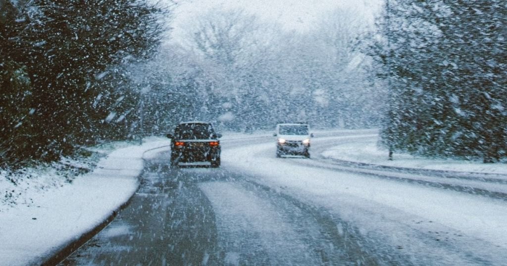 cars driving on a road while it's snowing