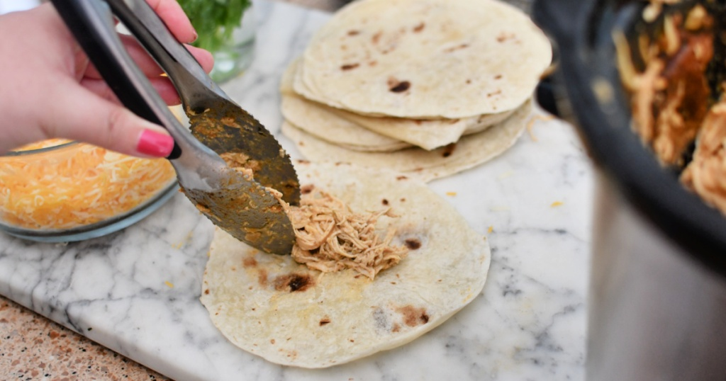 adding chicken to tortillas for taquitos