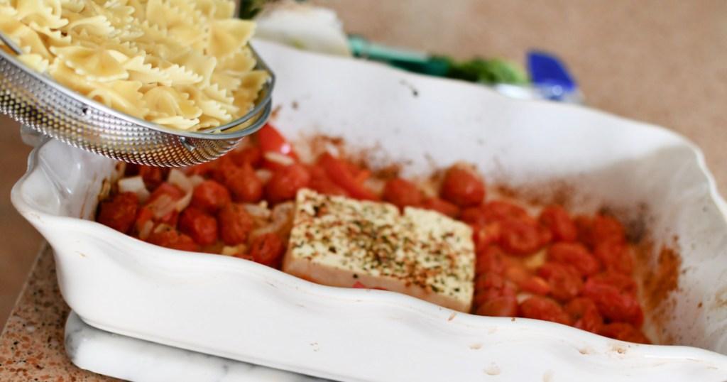 adding noodles into baked feta pasta