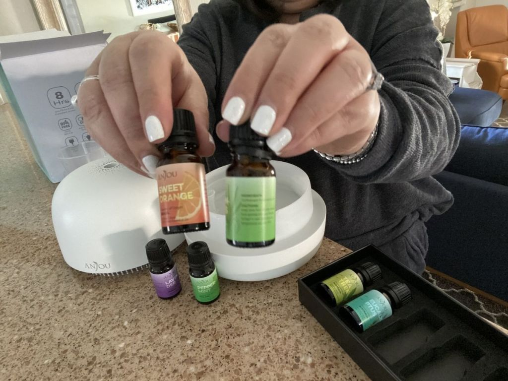 woman holding two essential oils
