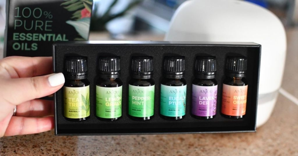 hand holding set of essential oils