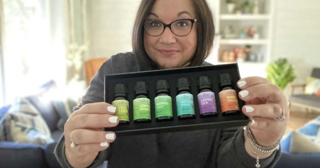 woman holding up essential oils set