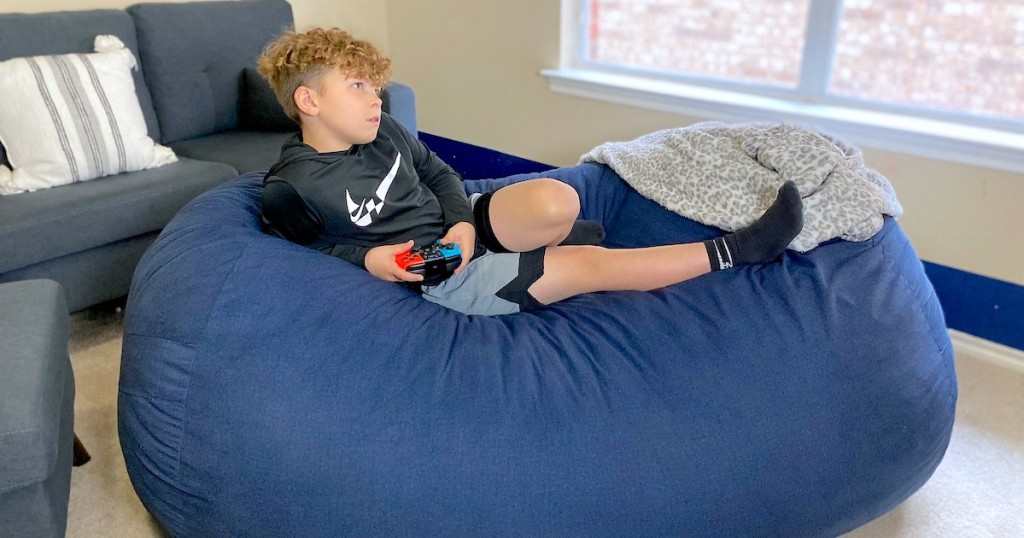 boy lounging on blue bean bag chair playing video games