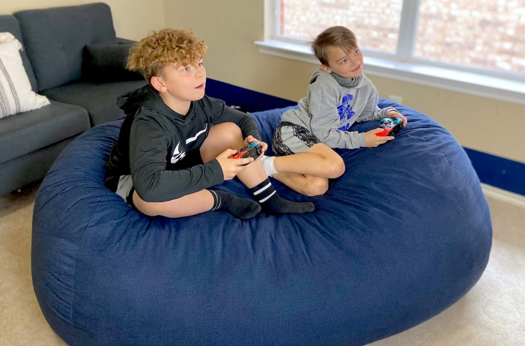 two boys sitting on large blue bean bag chair playing video games
