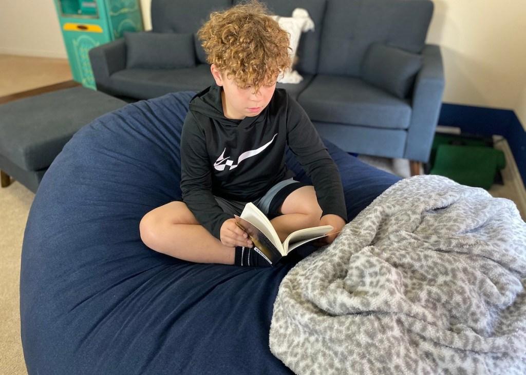 boy sitting on blue bean bag reading a book