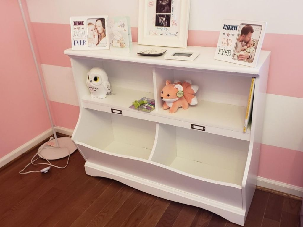 white storage shelf with picture frames on top
