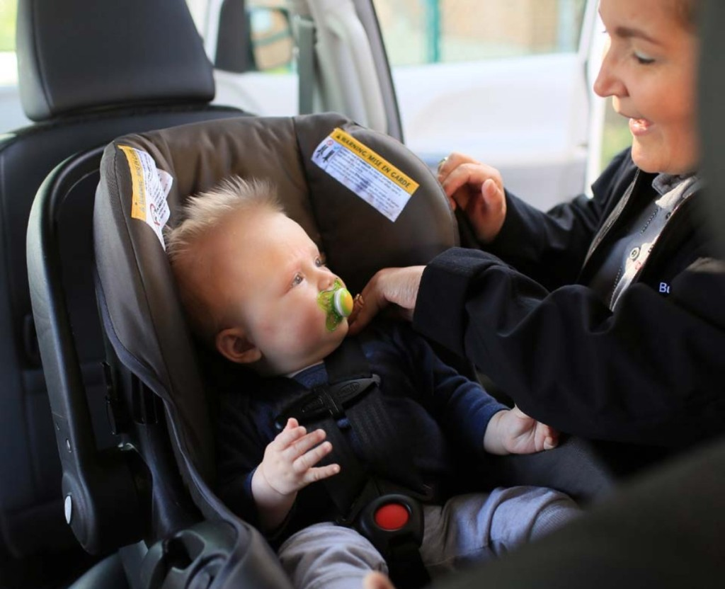 woman buckling baby in car seat