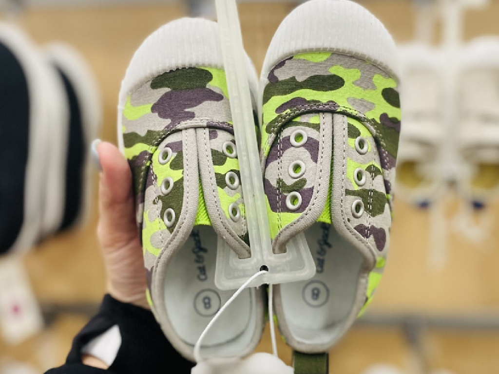 hand holding pair of kids shoes with camo design