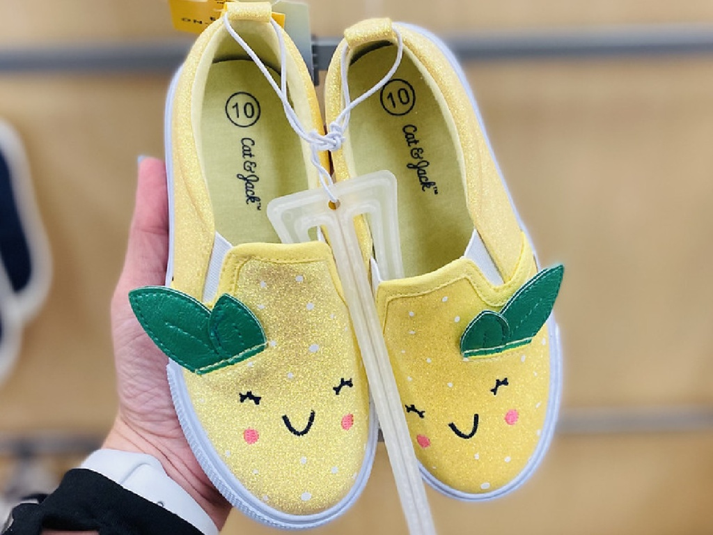 hand holding pair of yellow shoes for kids that look like lemons