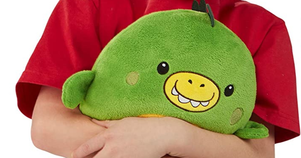 Green dinosaur huggle pet held by a child with a red short sleeve tee