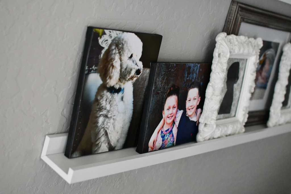 displaying diy photo canvases on a picture frame ledge
