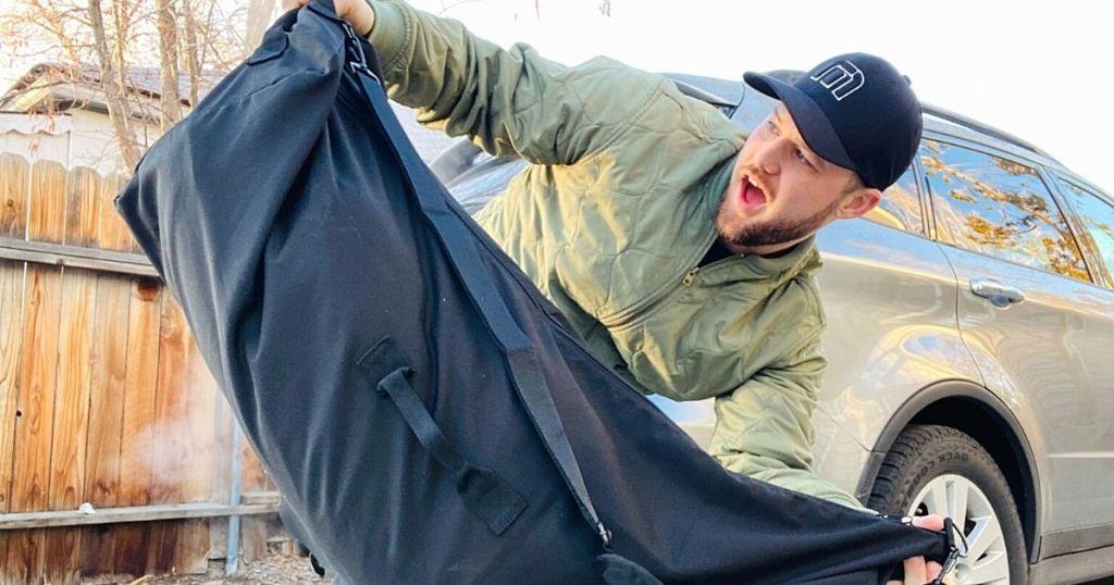 man holding black duffel bag