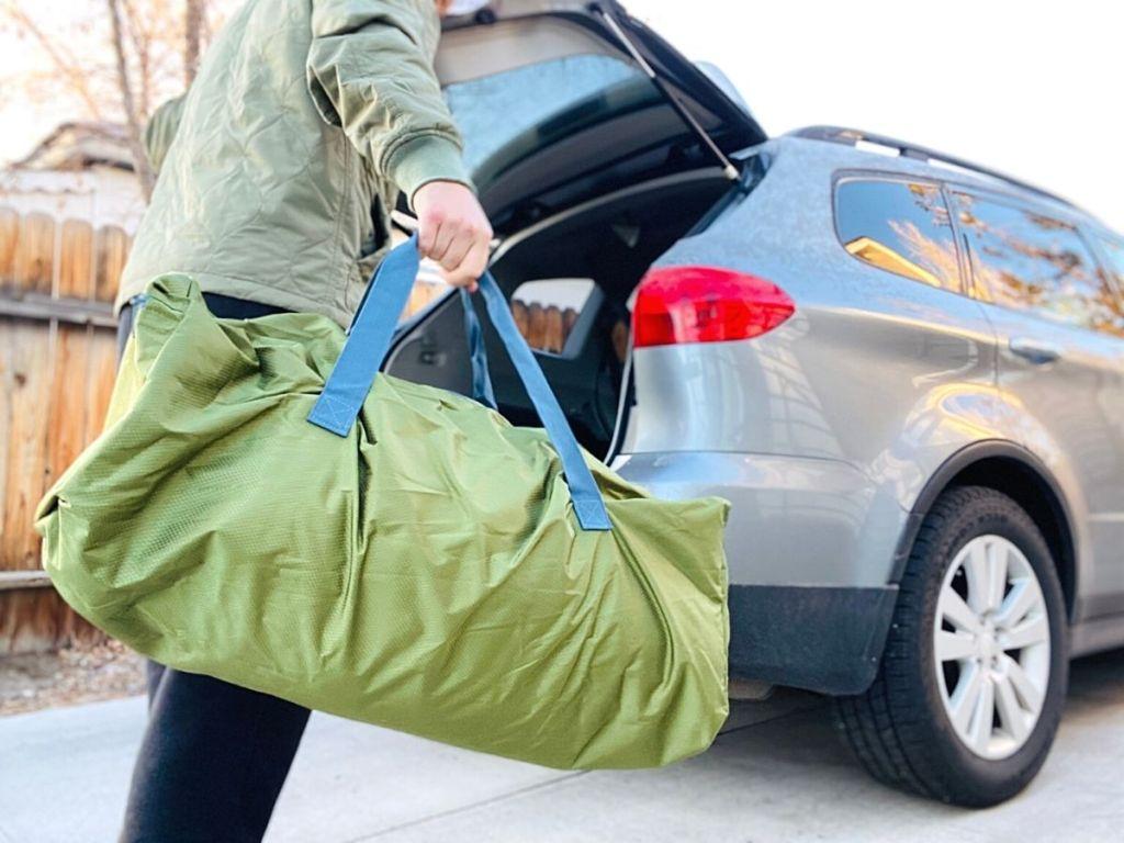 man holding green duffel bag