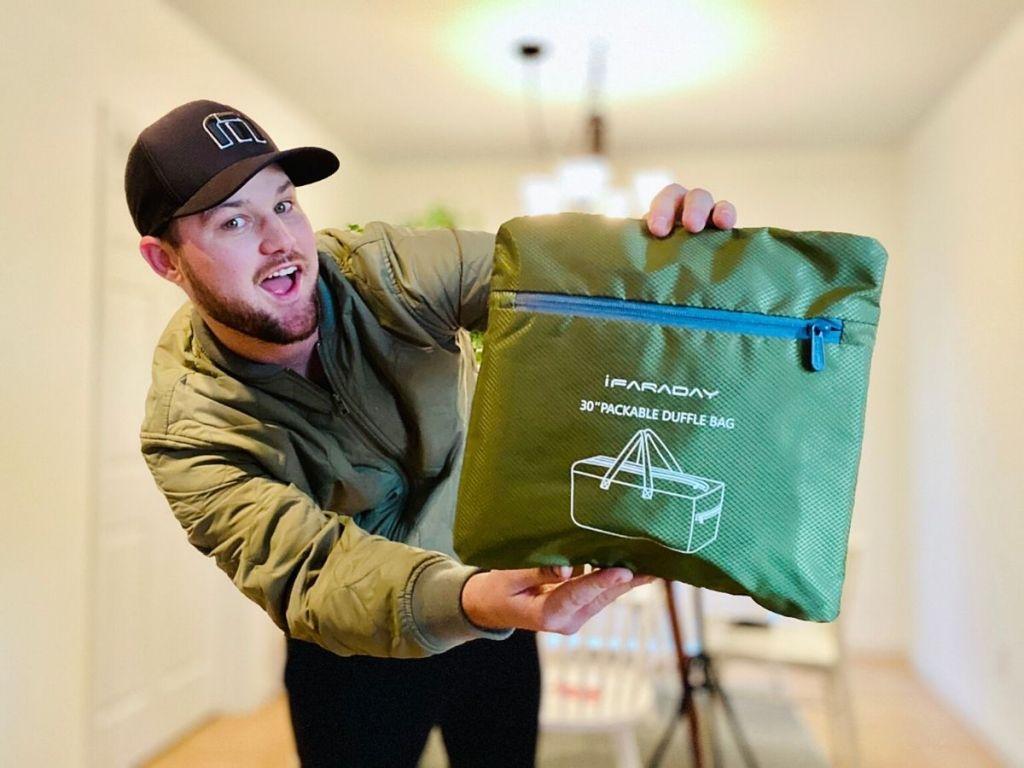 man holding duffel bag in compact bag