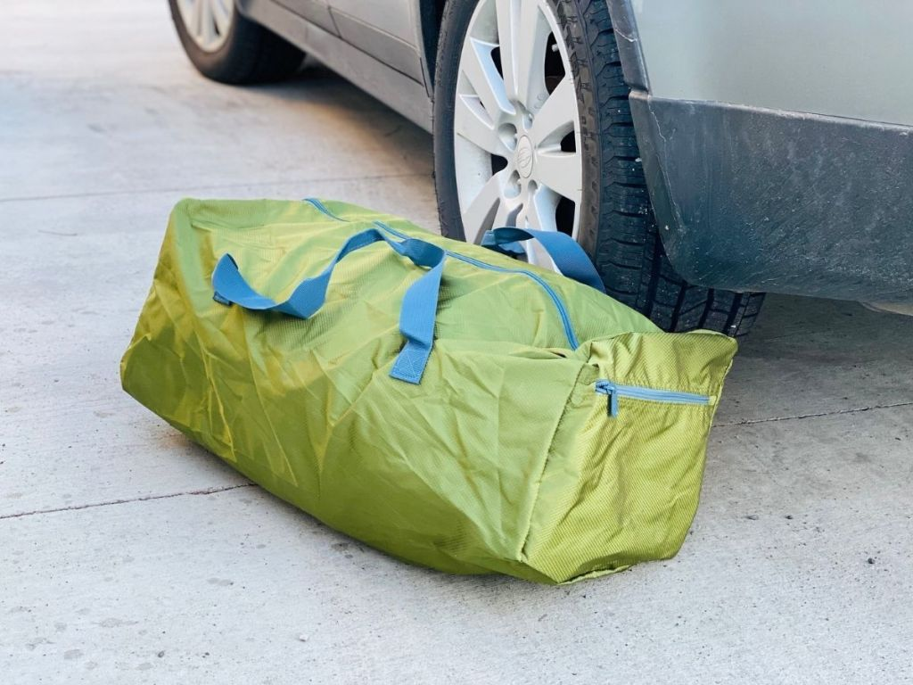 green and blue duffel bag on ground