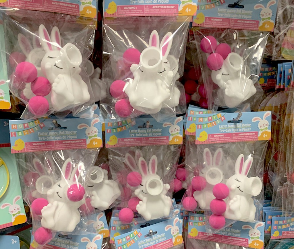 white bunnies with pink balls in bags hanging from store shelf