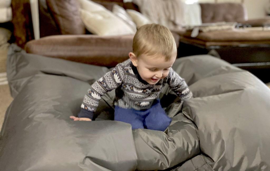 boy sitting on gray bean bag