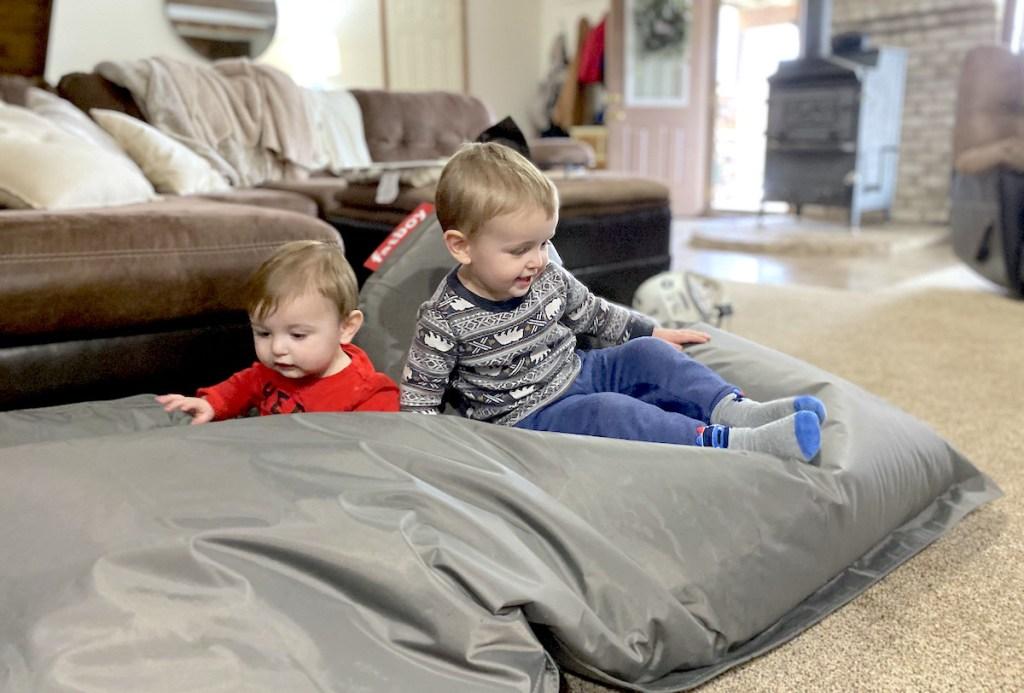 two boys sitting on huge gray bean bag on floor