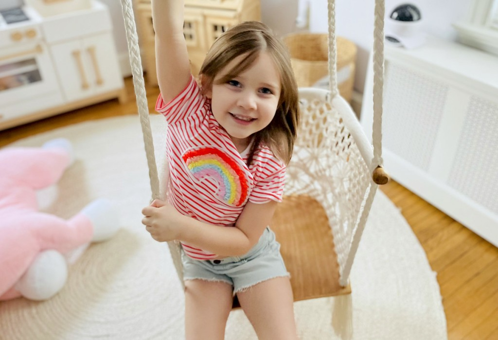 girl sitting on macrame swing wearing cheap kids clothes from garanimals