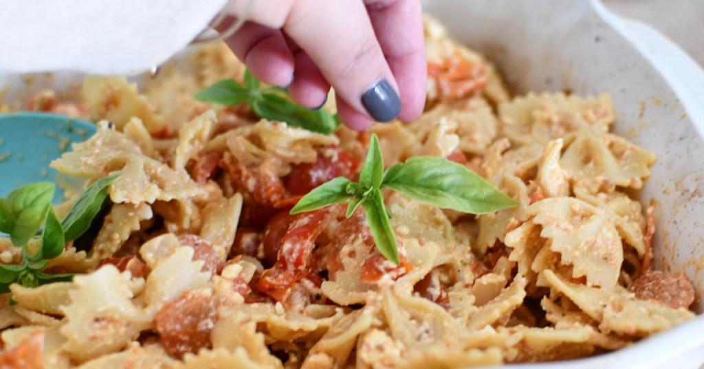 garnishing feta pasta with fresh basil