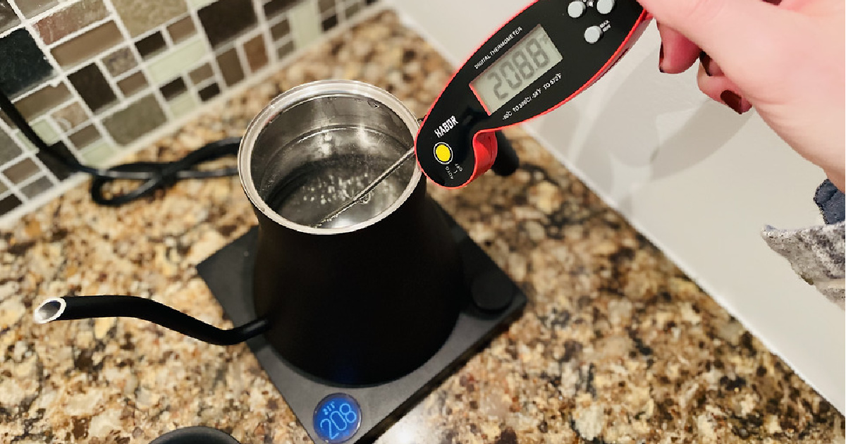 woman using food thermometer to check water temperature