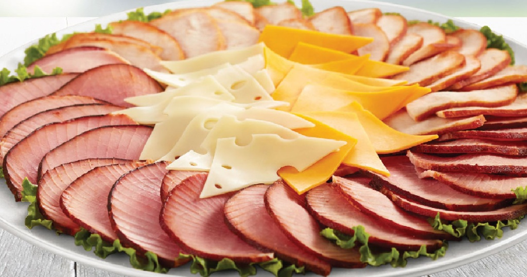 large plate with slices of hams and cheese