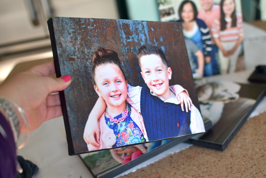 holding DIY photo canvas of 2 kids