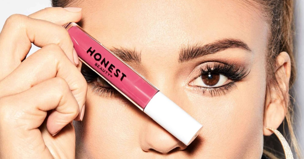honest beauty liquid lipstick in fearless in hand over face