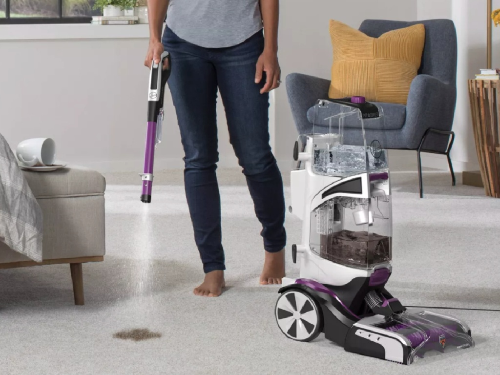 woman pointing hose down of hoover smartwash carpet cleaner on carpet
