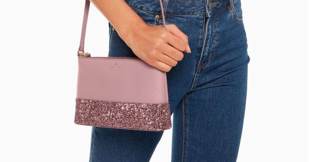 woman holding Kate Spade pink glitter crossbody bag