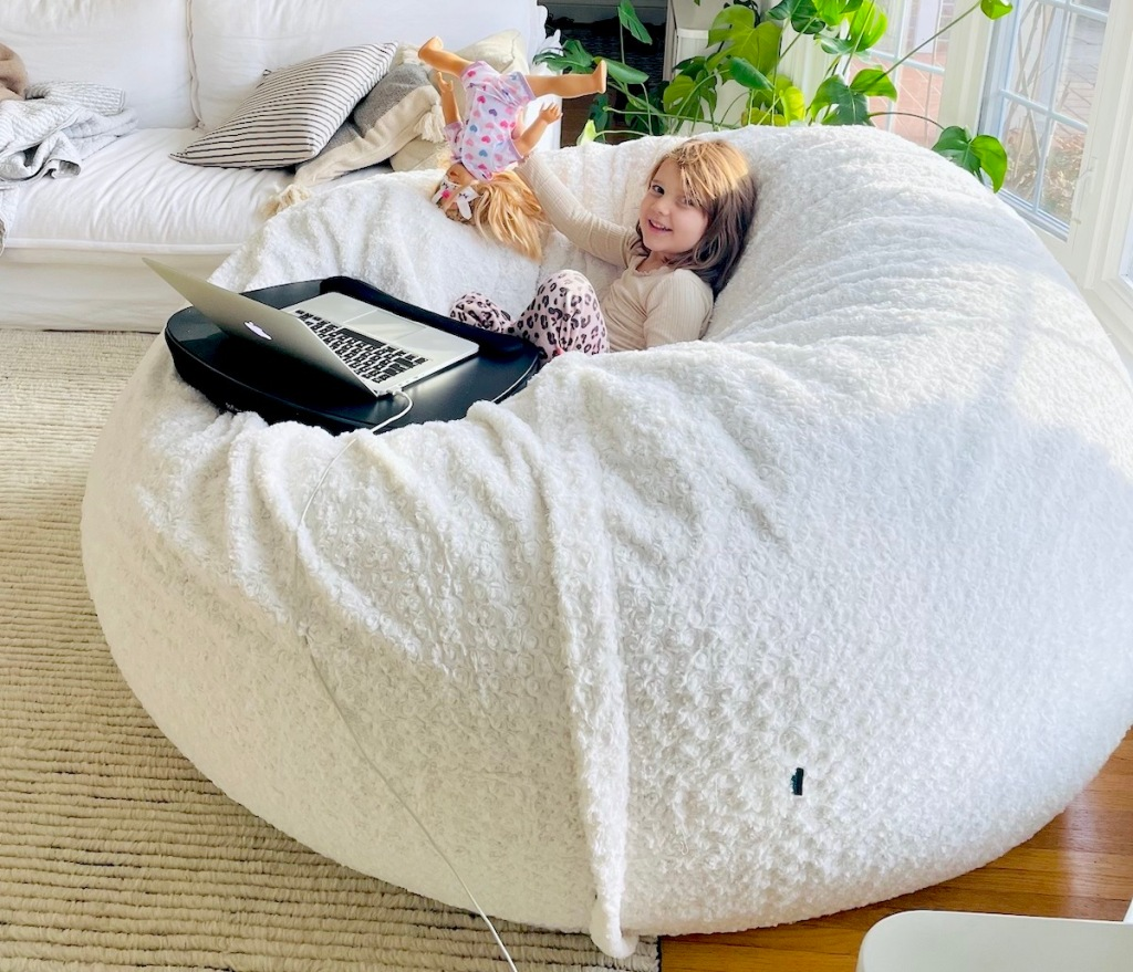 girl sitting on white giant lovesac bean bag with laptop and doll