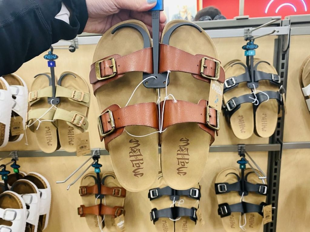 hand holding tan flat bed sandals