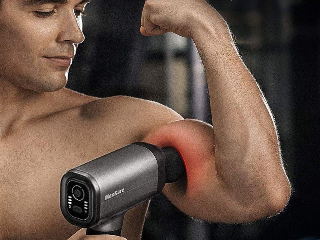man using massage gun on bicep