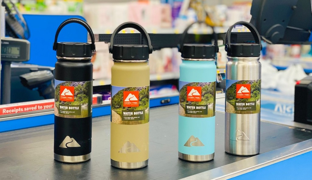 row of different colored ozark trail water bottles on store cash register belt