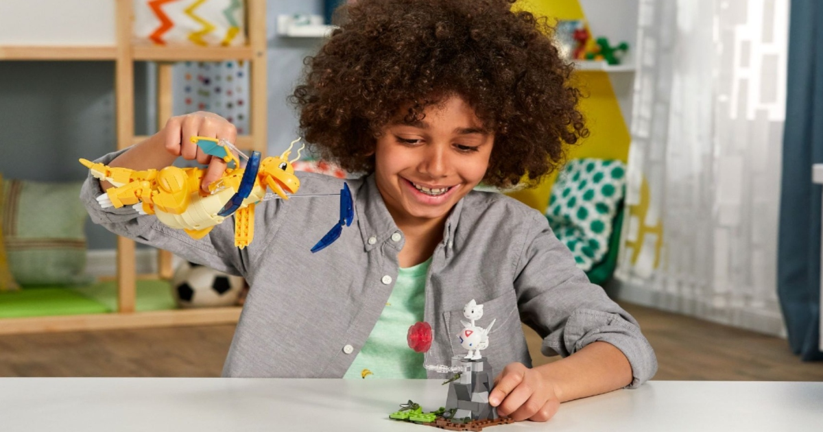 Boy playing at a table with Pokemon Dragonite playset