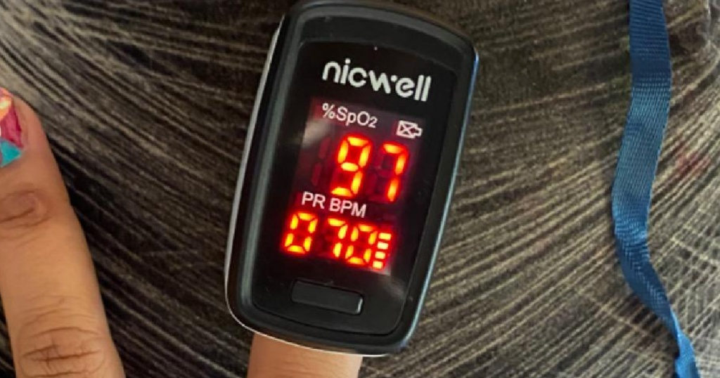 pulse oximeter on finger with red LED display