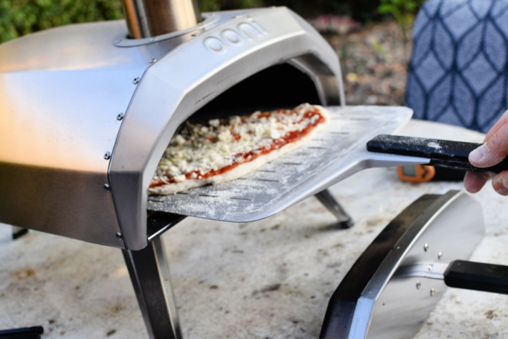 putting a pizza into the Ooni pizza oven