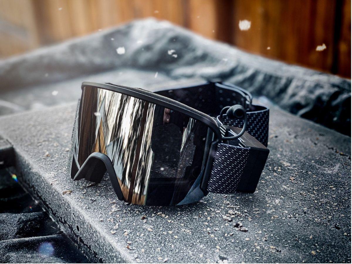 Ski goggles sitting on black surface
