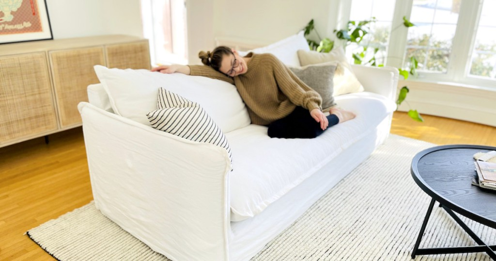 woman laying on white sofa in living room