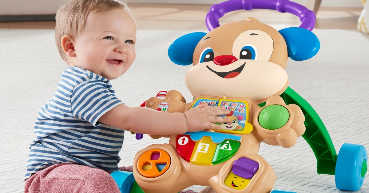 toddler sitting on the floor playing with the toys on the front of the Fisher Price Walker