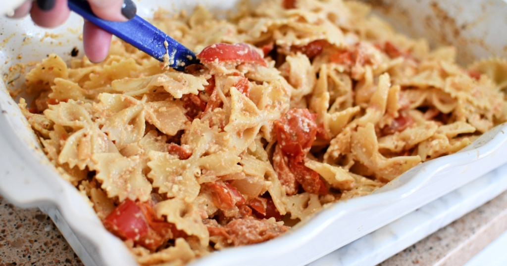 stirring melted feta bow tie pasta