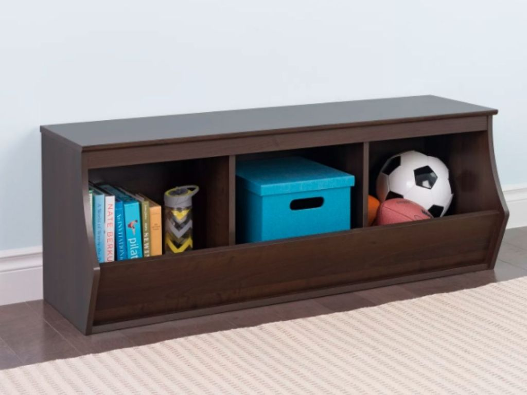 brown storage bench holding books and sports balls