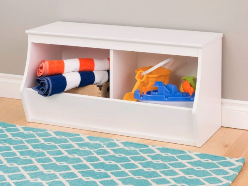 white storage bench holding towels and beach toys