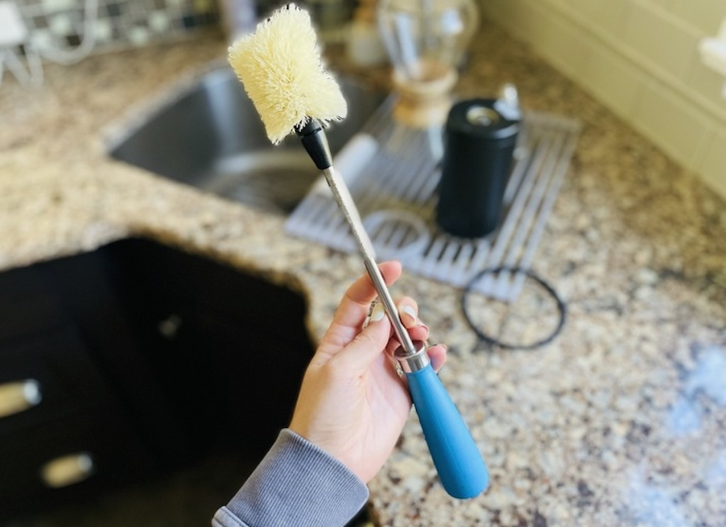 hand holding blue bottle brush in kitchen over sink