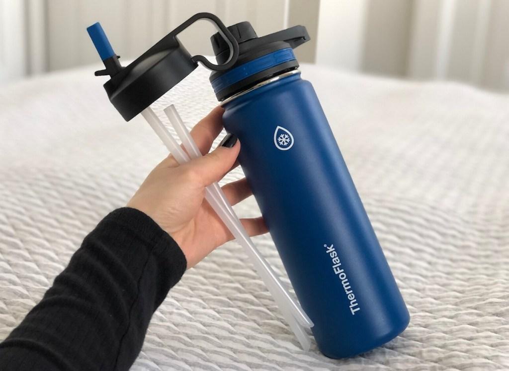 hand holding blue water bottle on top of stripe blanket