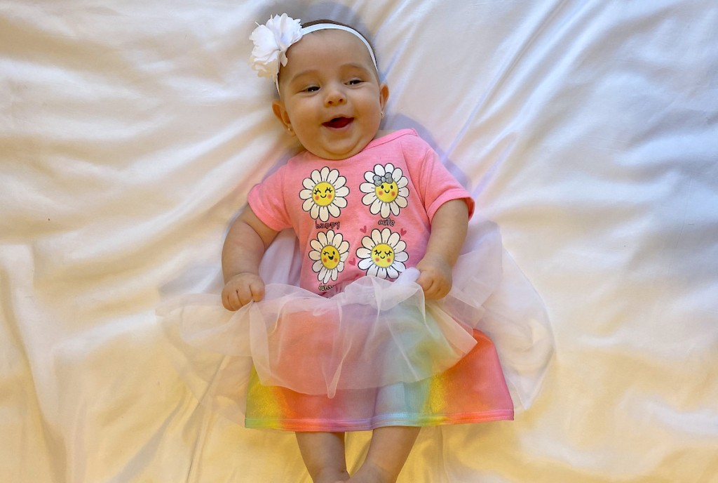 baby girl laying on white blanket with tutu skirt flower shirt and headband
