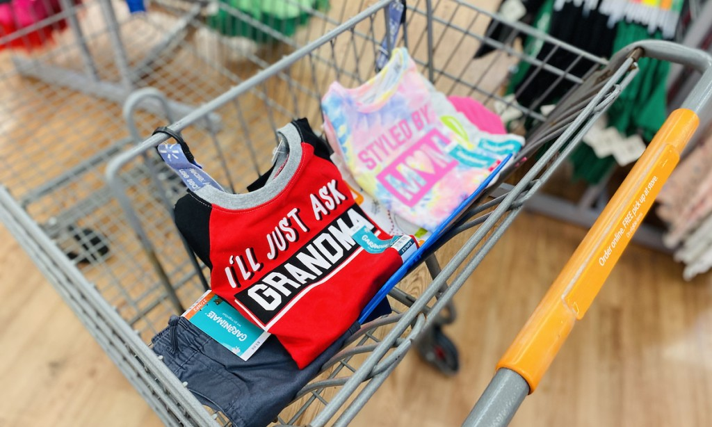 pile of colorful kids clothes sitting in top of store cart