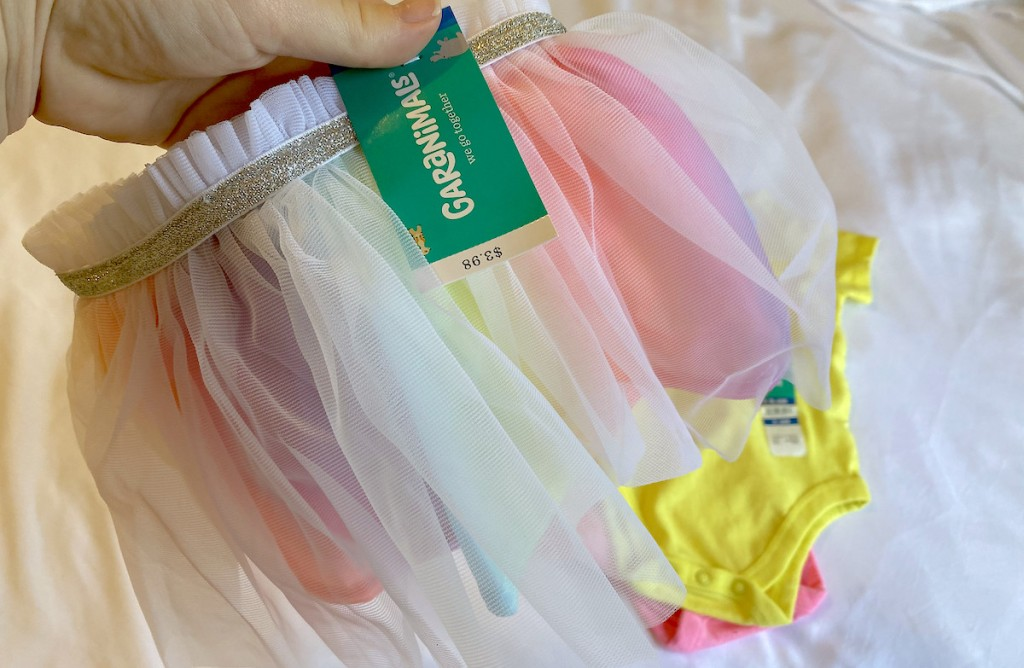 hand holding a rainbow tulle skirt with garanimals tag