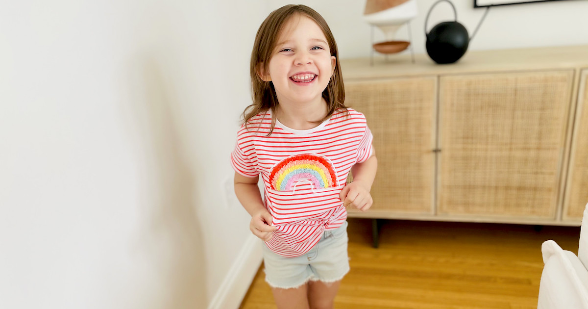 girl wearing colorful rainbow shirt smiling
