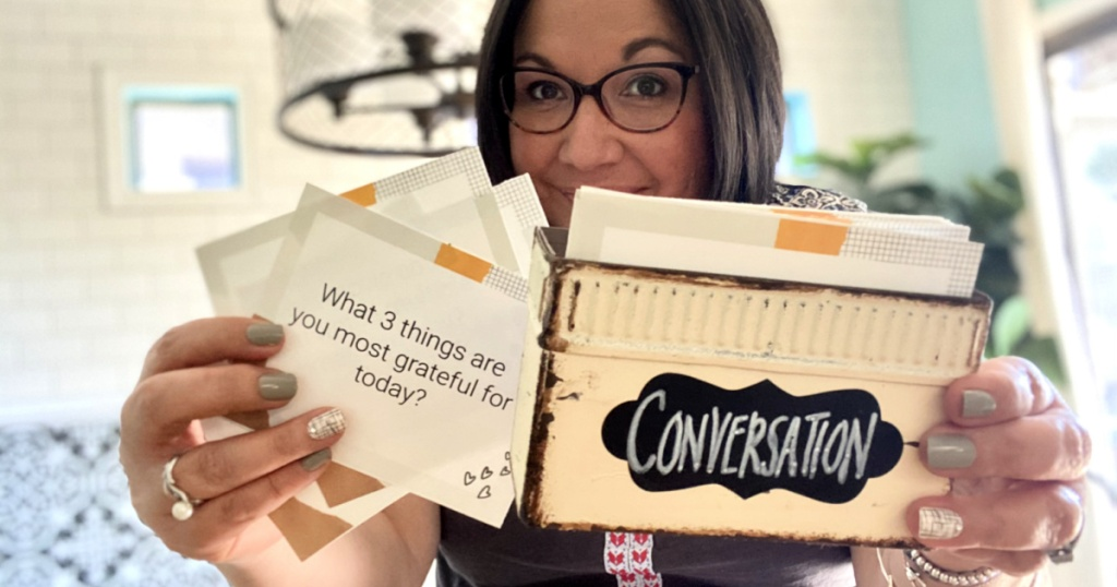 woman holding conversation cards
